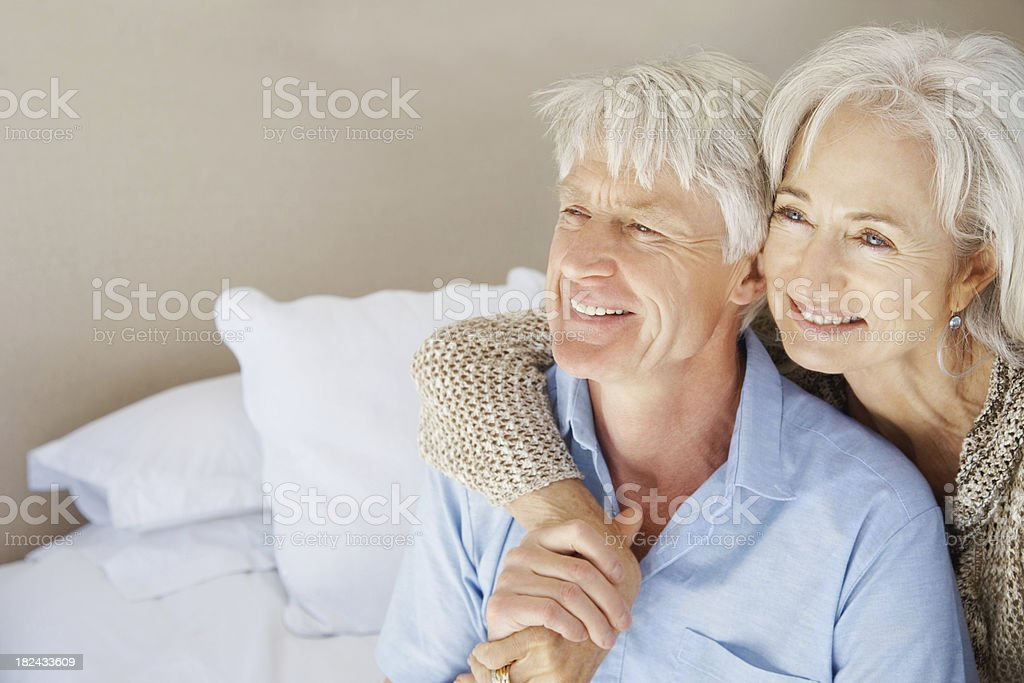 Senior couple sitting together on the bed and looking away royalty-free stock photo