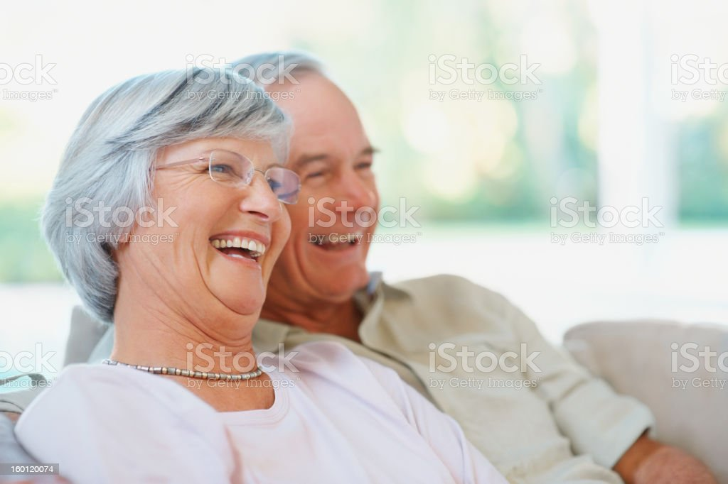 Senior couple sitting together on the couch royalty-free stock photo