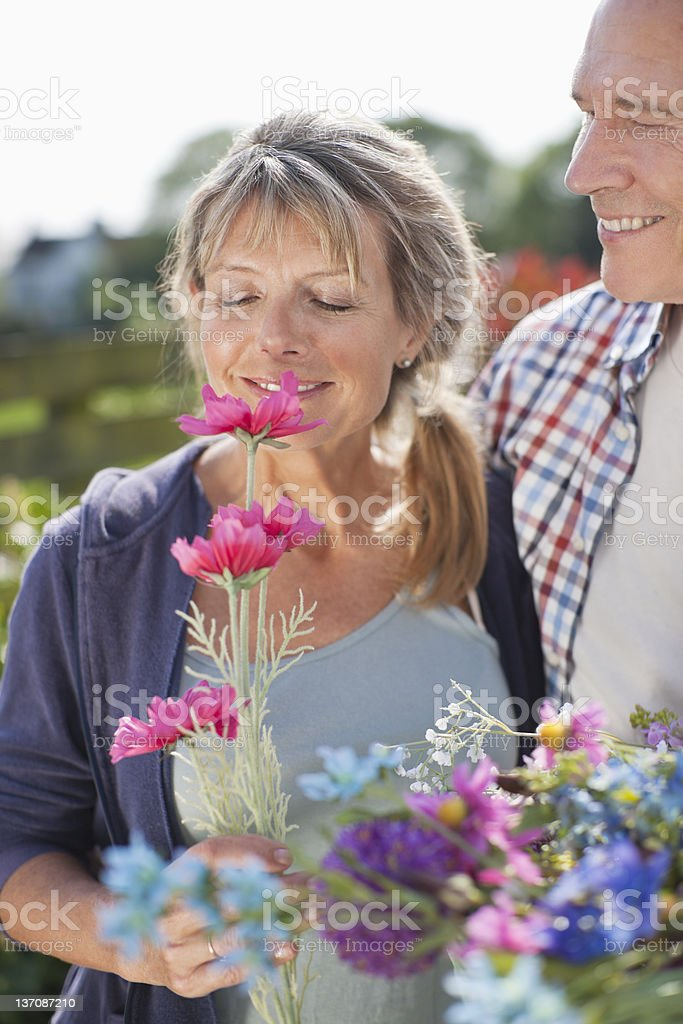 Senior couple smelling flowers in garden royalty-free stock photo