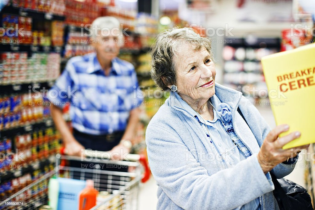 Senior couple smile on finding favourite cereal in supermarket stock photo