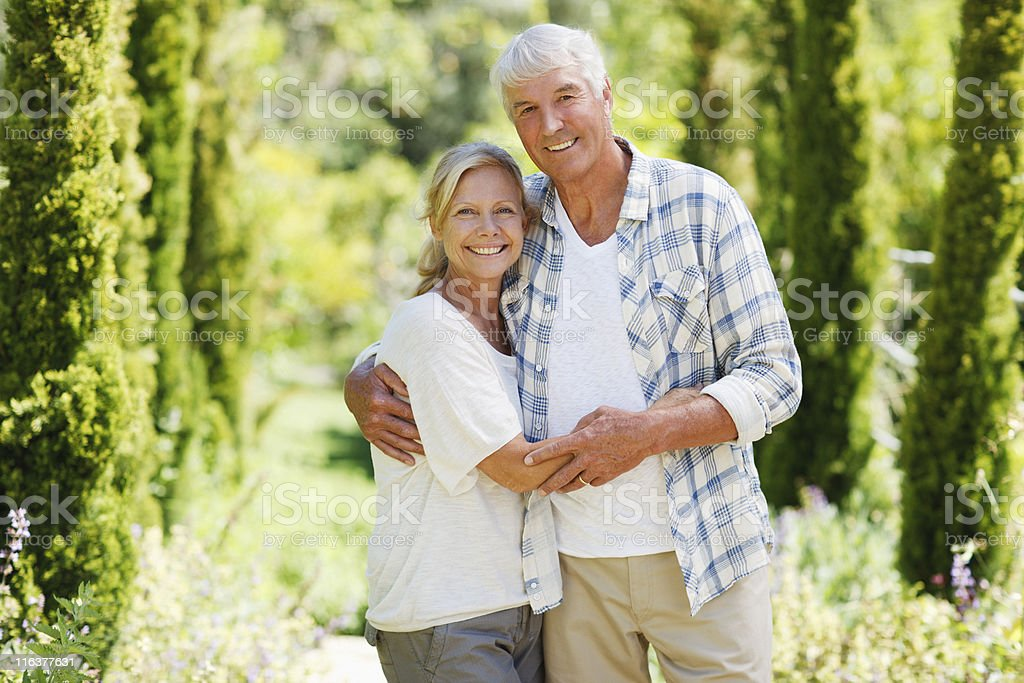 Senior couple smiling in garden royalty-free stock photo
