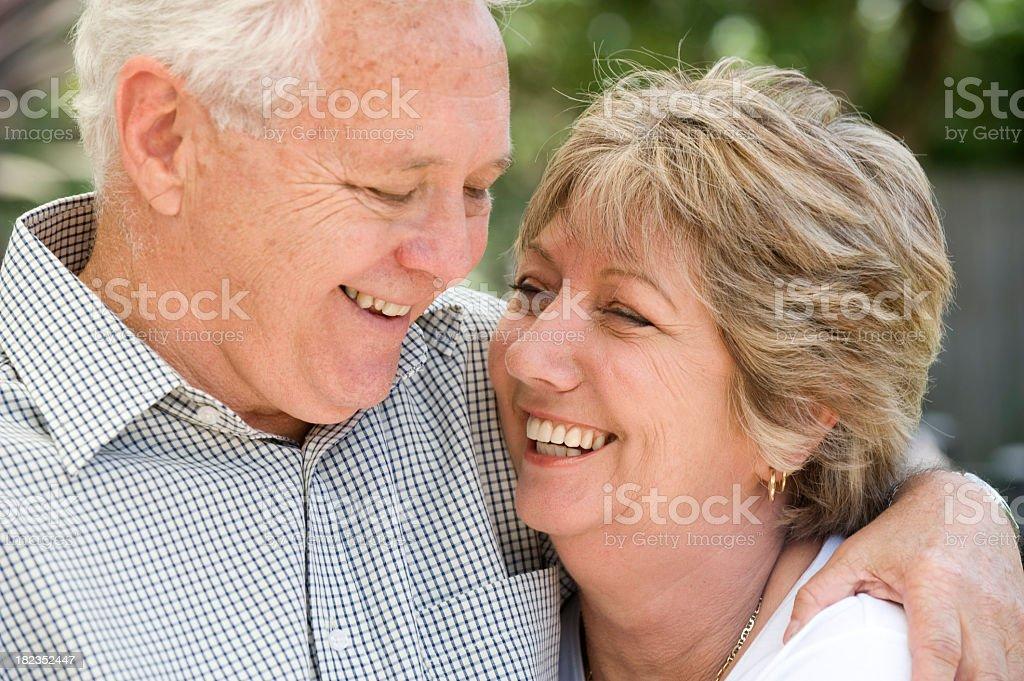 Senior couple smiling portrait outdoors. Soft focus background royalty-free stock photo