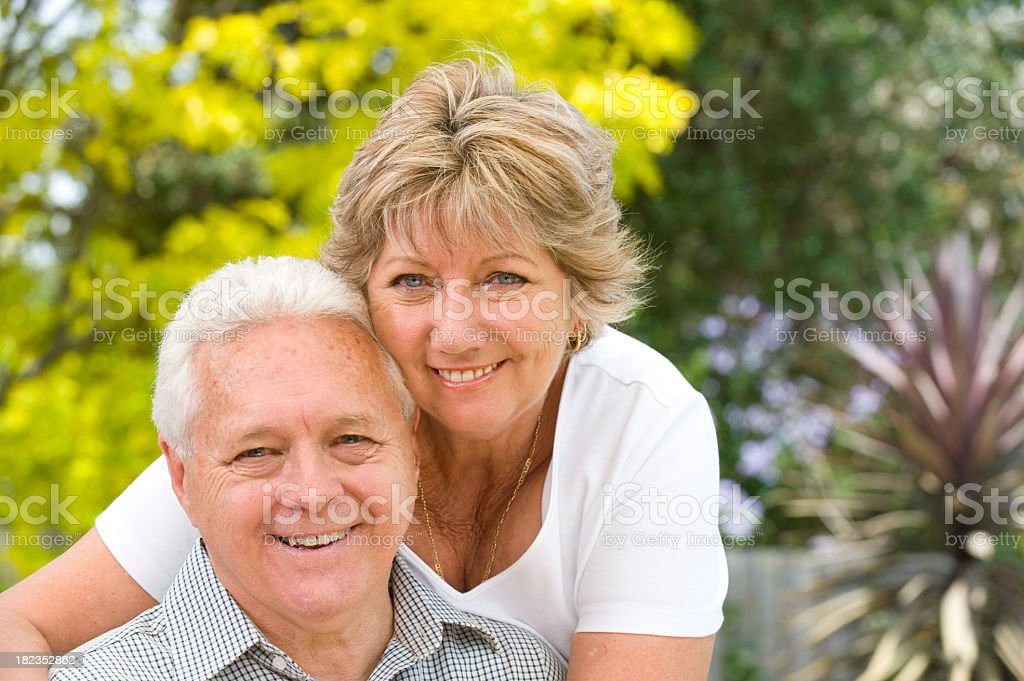 Senior couple smiling with blurred garden background royalty-free stock photo