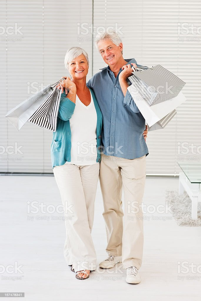 Senior couple smiling with shopping bags in hand royalty-free stock photo