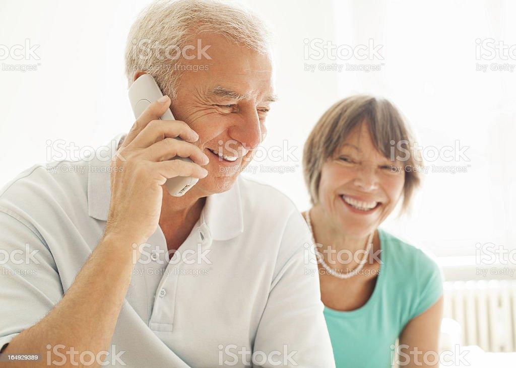 Senior couple speaking on the phone stock photo
