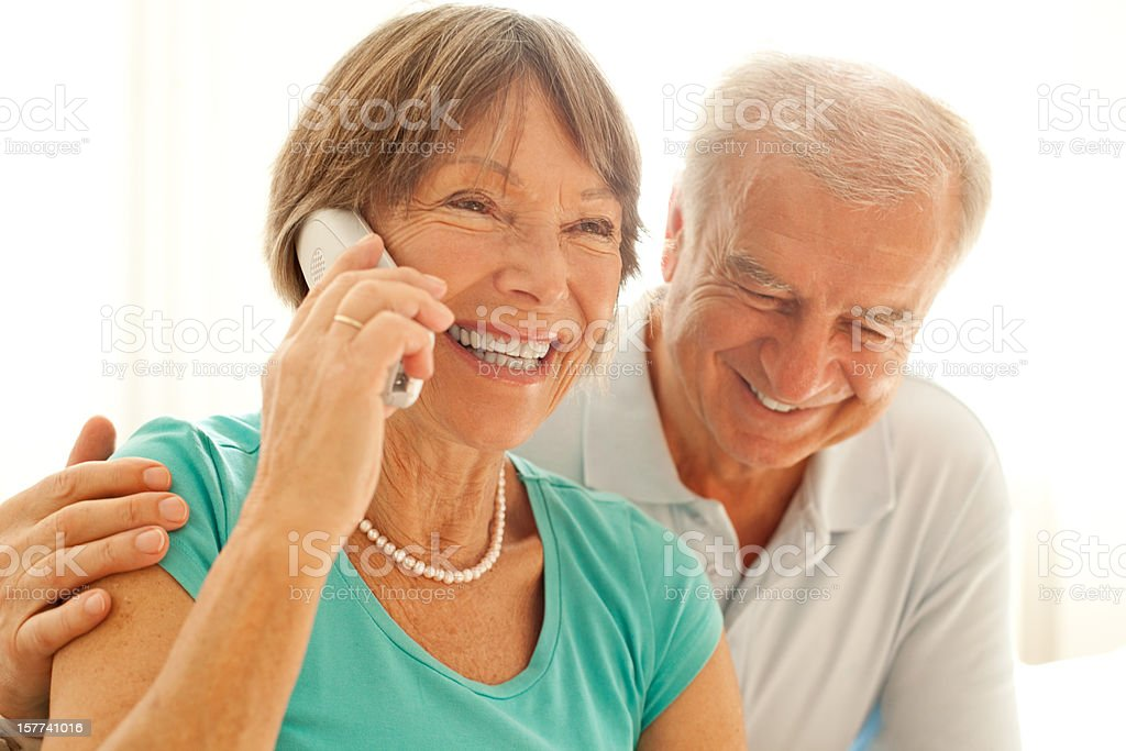 Senior couple speaking on the phone with their loved ones stock photo