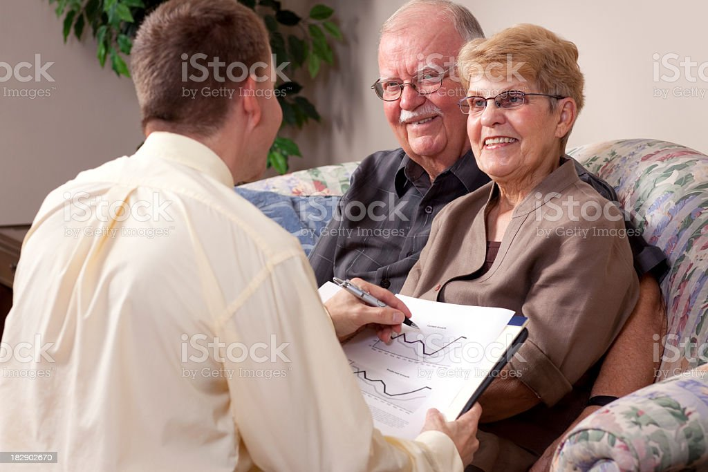 Senior couple speaking with a man holding a book with charts stock photo