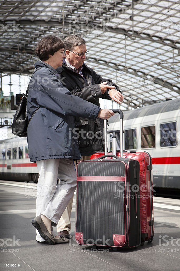 senior couple standing on the Railroad Station Platform and waiting...