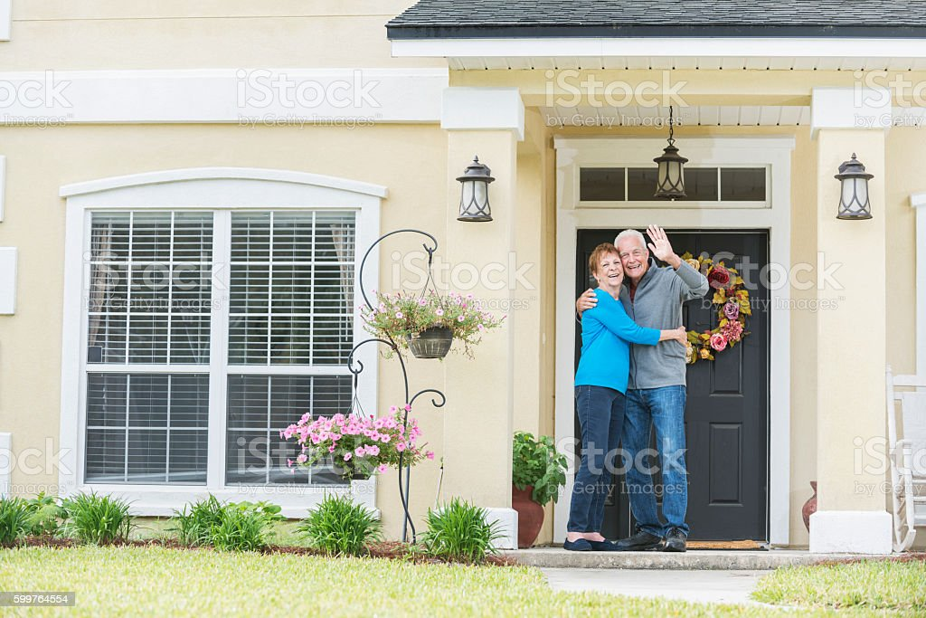Senior couple standing at front door of home waving stock photo