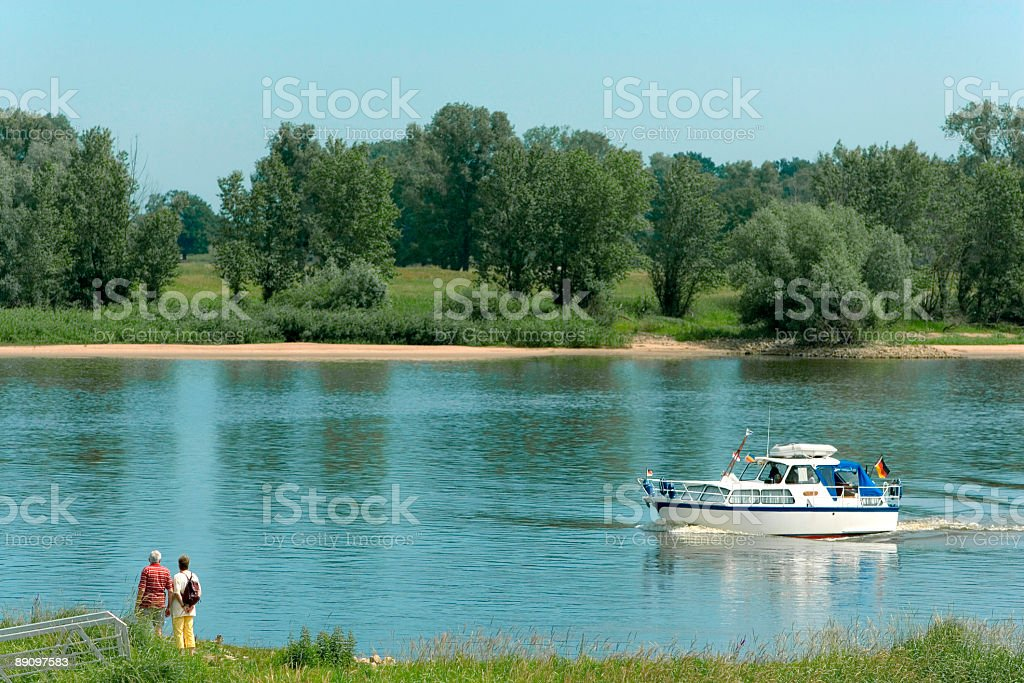 Senior couple standing at water´s edge of Elbe river (XL) royalty-free stock photo