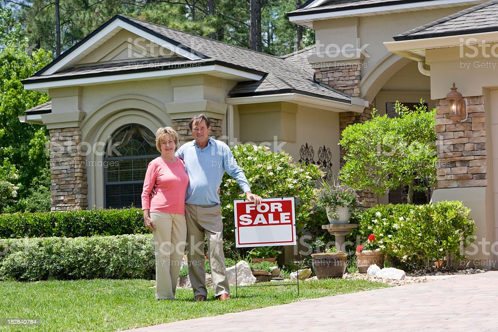 Senior couple standing by For Sale sign on house lawn royalty-free stock photo