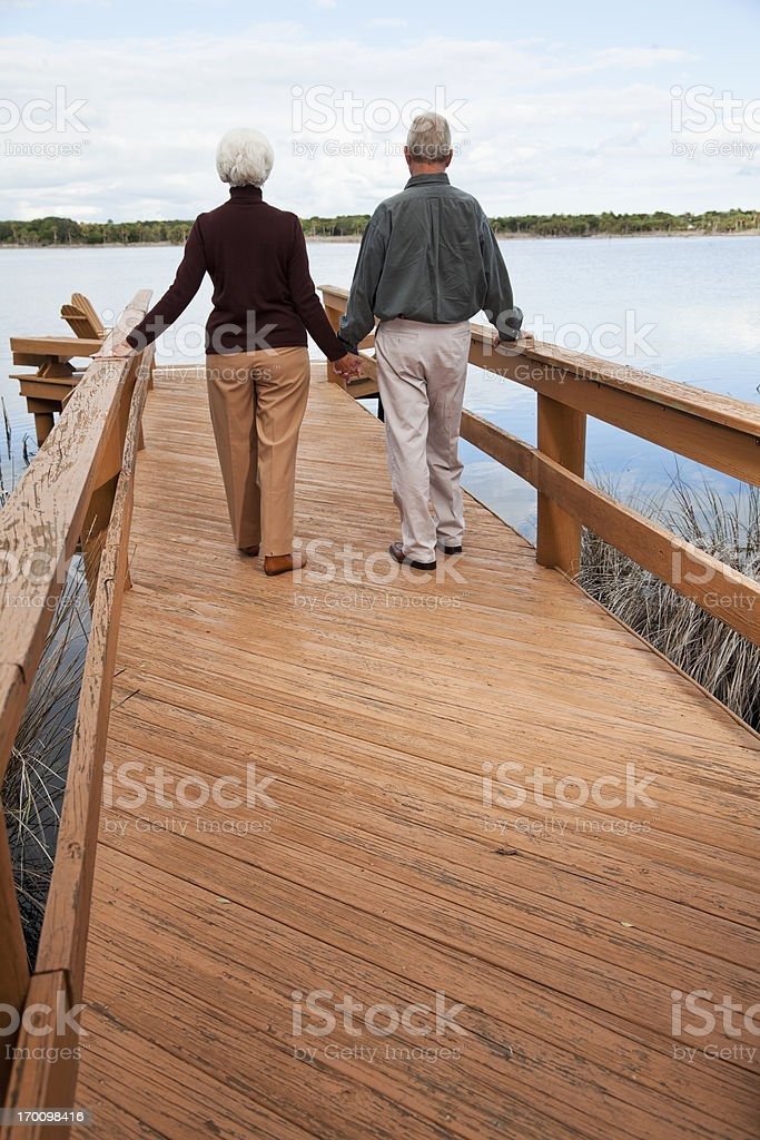 Senior couple standing by water stock photo