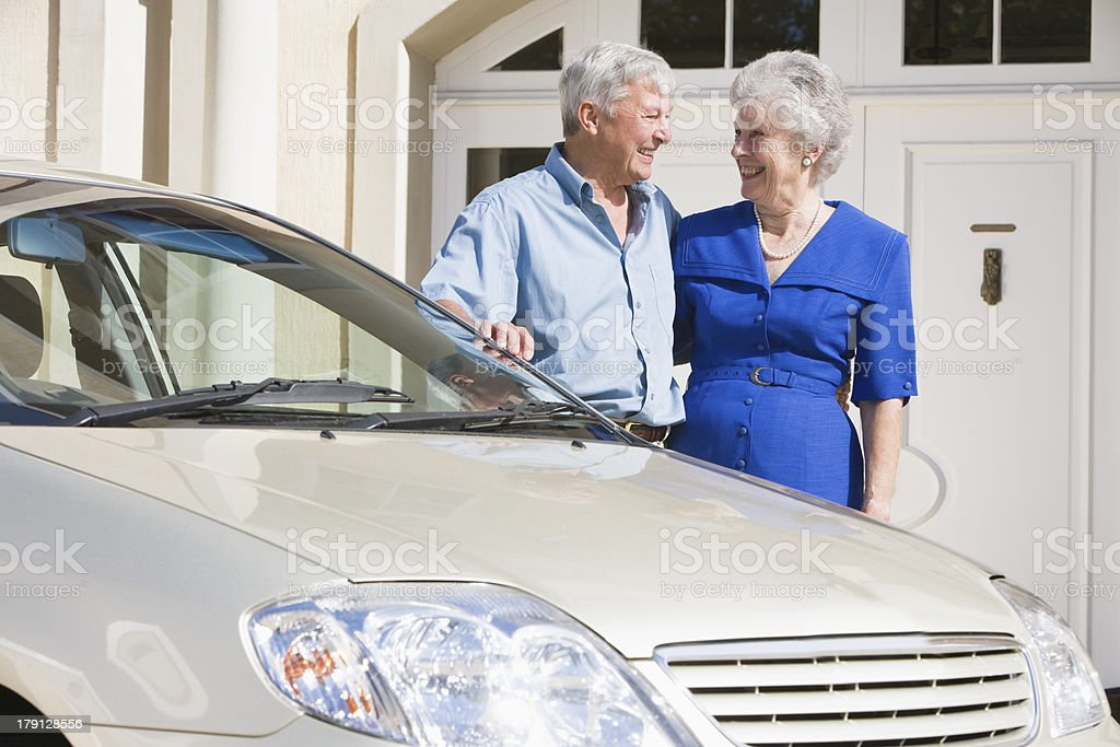 Senior couple standing next to car royalty-free stock photo