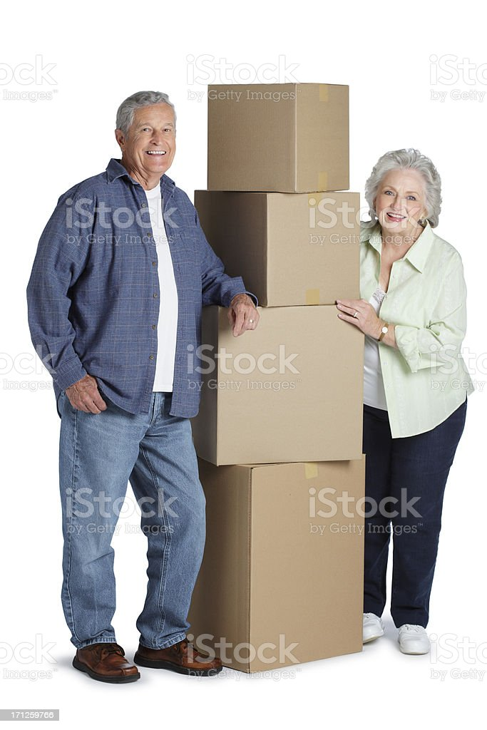 Senior couple standing next to stack of boxes royalty-free stock photo