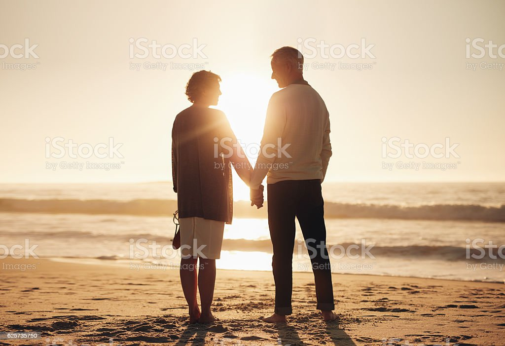Senior couple standing on a beach together stock photo