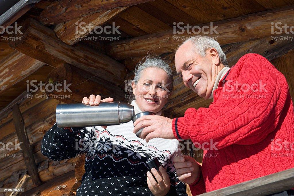 Senior couple standing on balcony of log cabin, smiling, portrait stock photo