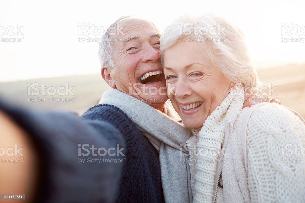 Senior Couple Standing On Beach Taking Selfie stock photo