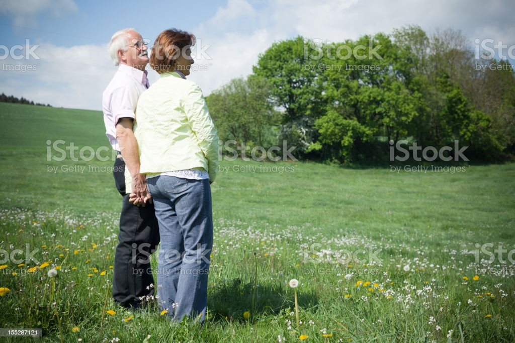 Senior couple standing on blooming meadow in spring royalty-free stock photo