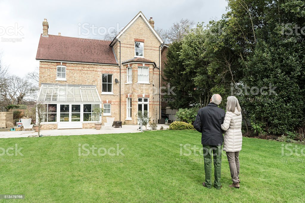 Senior couple standing on lawn outside house stock photo