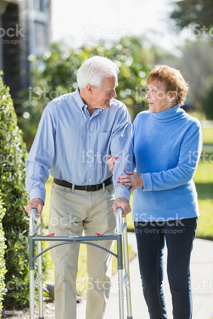 Senior couple standing outdoors, man using walker stock photo