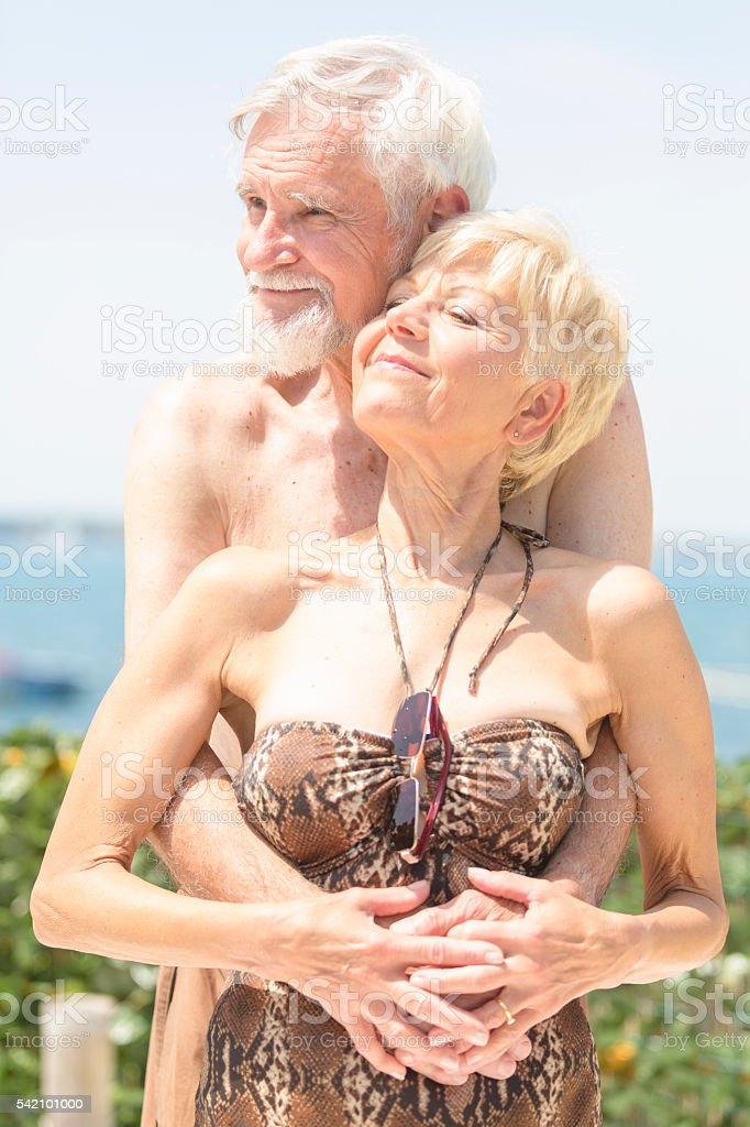 Senior couple sunbathing together stock photo