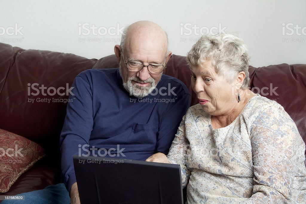 Senior couple surprised by what they see on Internet royalty-free stock photo