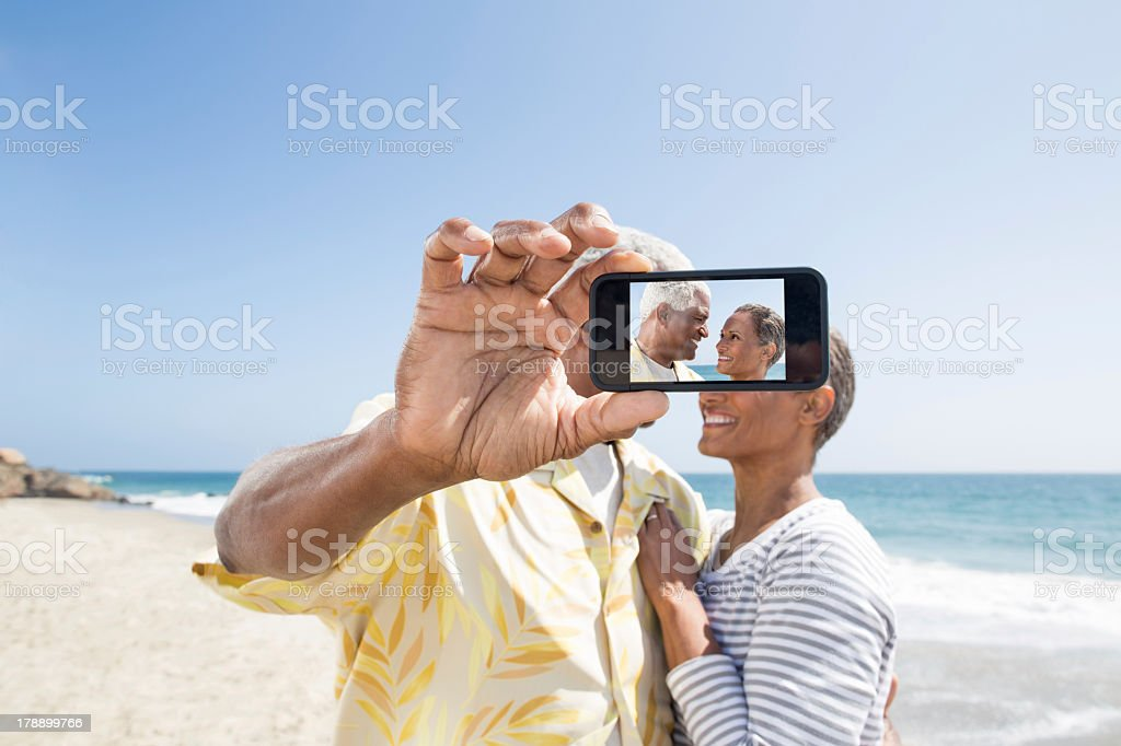 Senior couple taking a picture on the beach royalty-free stock photo