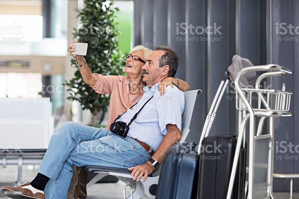 Senior Couple taking a selfie in the airport stock photo