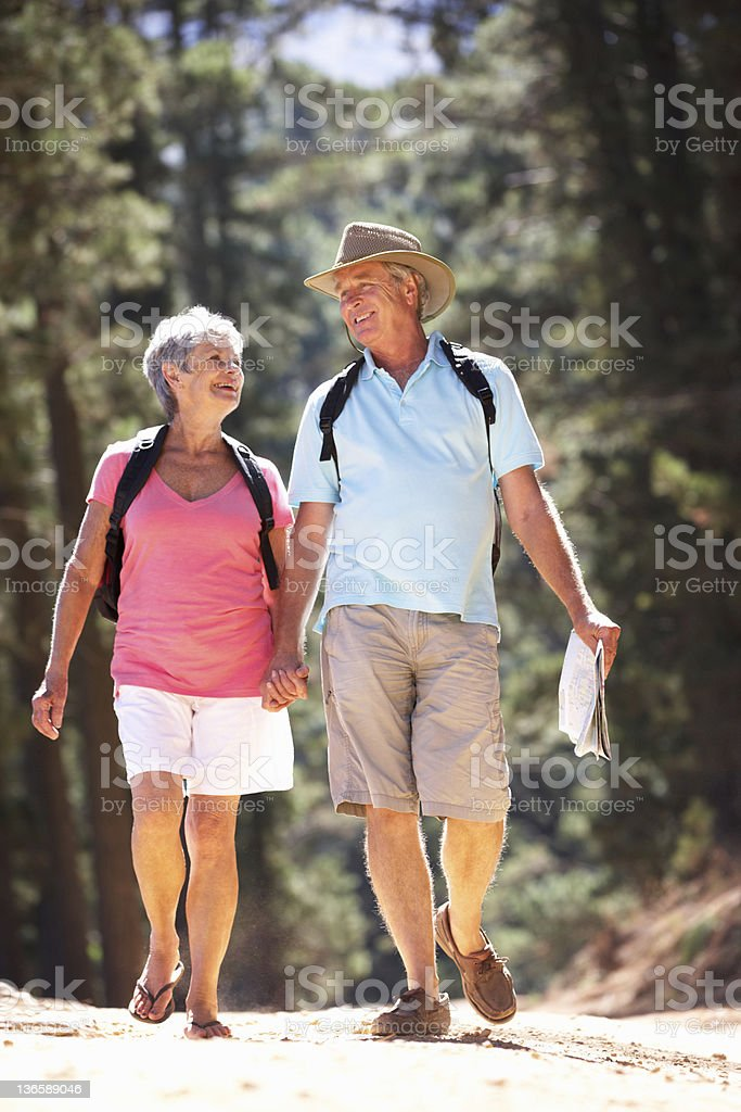 Senior couple taking a walk in the woods royalty-free stock photo