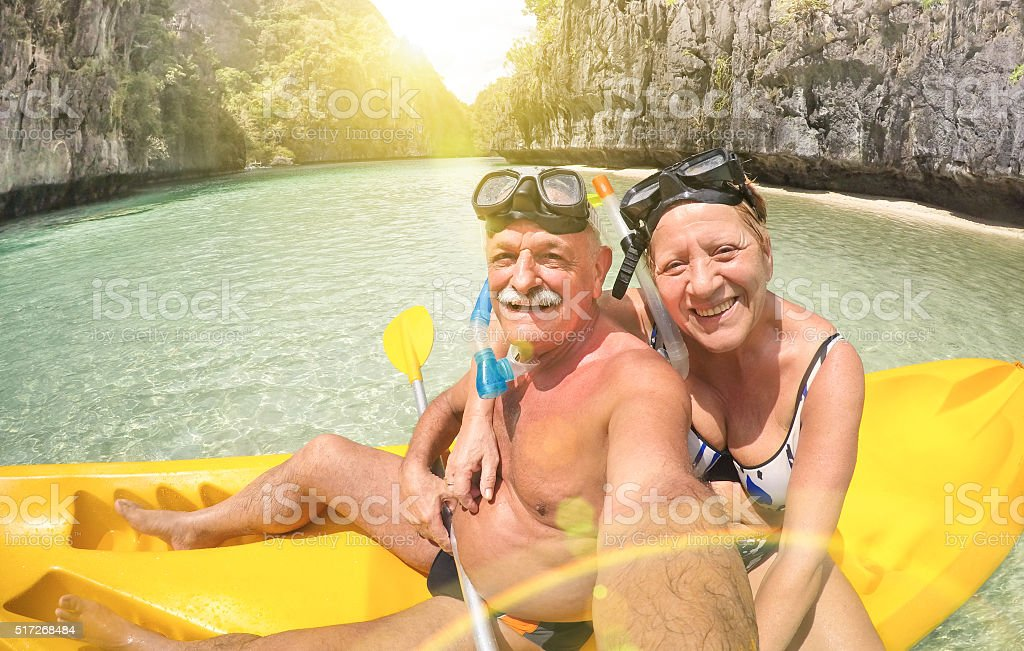 Senior couple taking selfie on kayak in El Nido lagoon stock photo