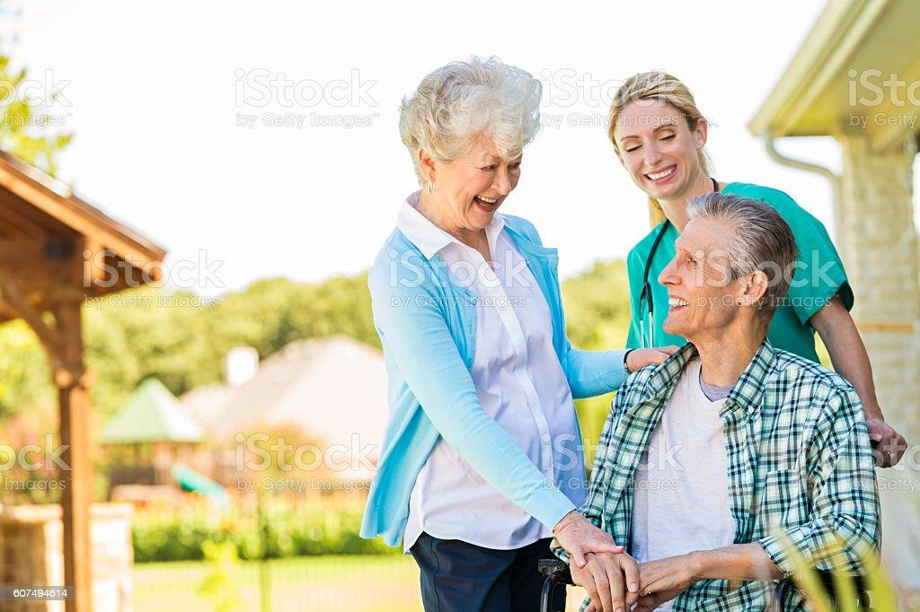 Senior couple talk with home healthcare nurse stock photo