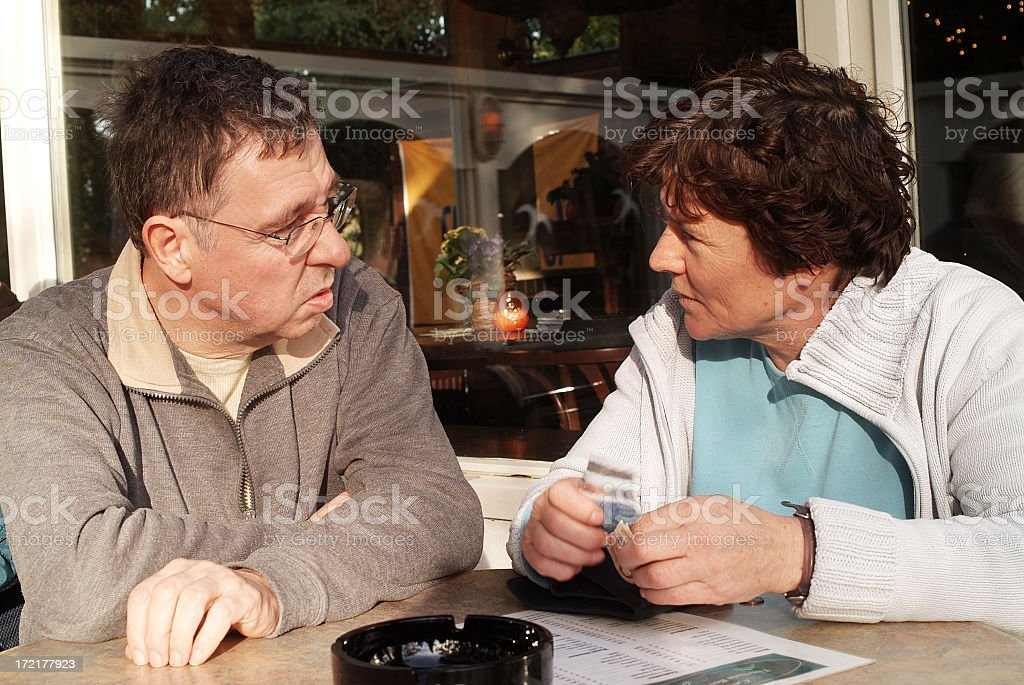Senior couple talking about money at restaurant table royalty-free stock photo