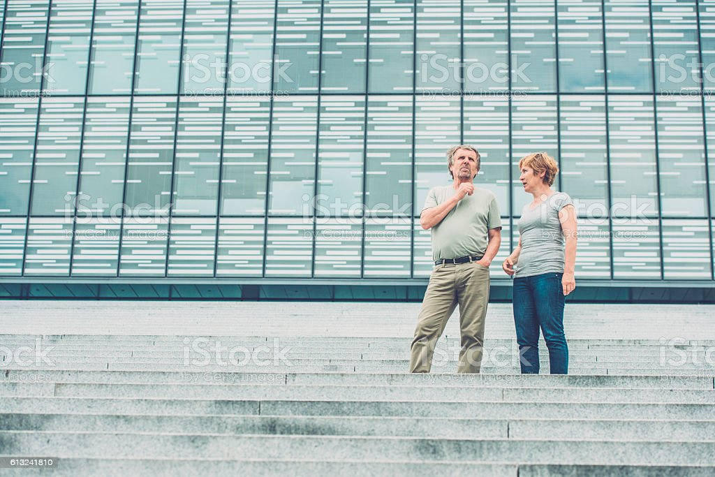 Senior couple talking in front of business building stock photo