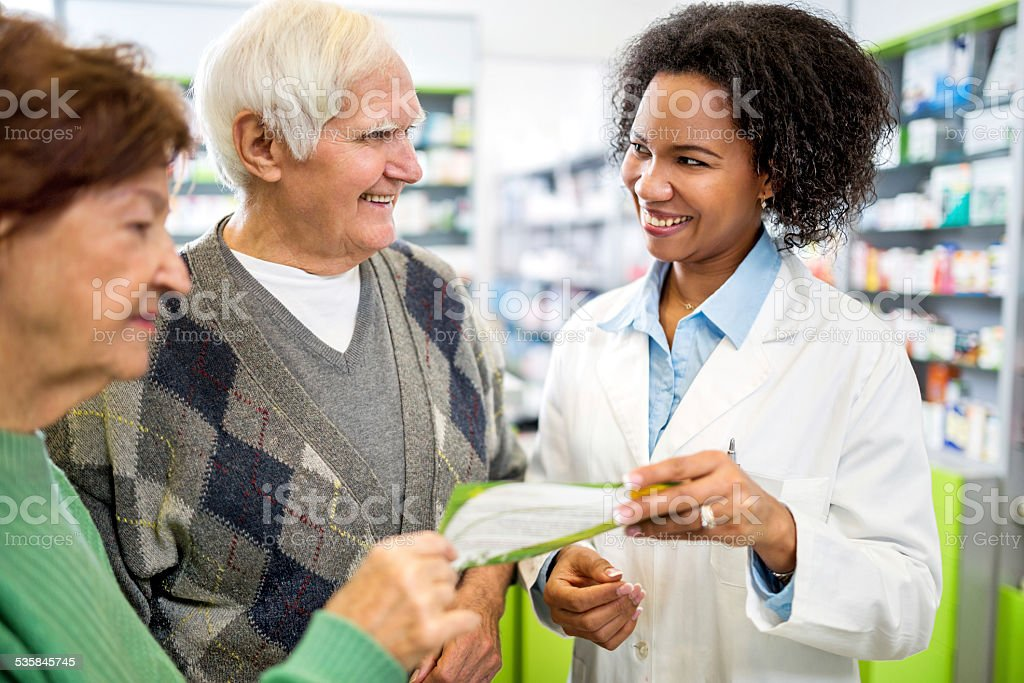 Senior couple talking with African American pharmacist. stock photo
