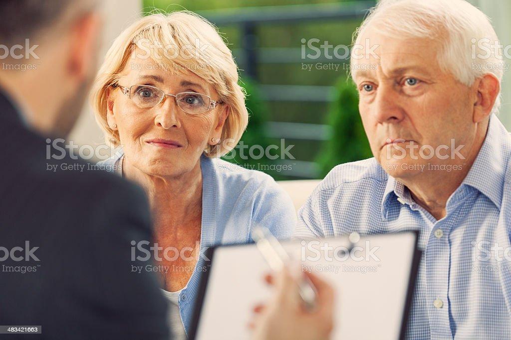 Senior couple talking with financial advisor stock photo