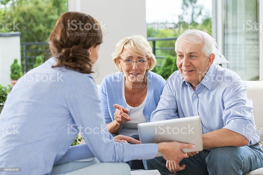 Senior couple talking with insurance agent stock photo
