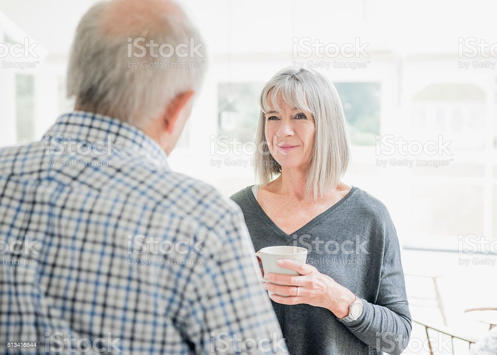 Senior couple talking, woman is holding coffee cup stock photo