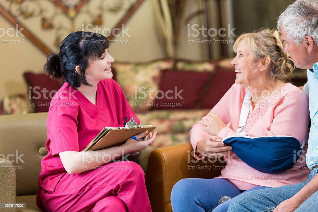 Senior couple talks with home healthcare nurse stock photo