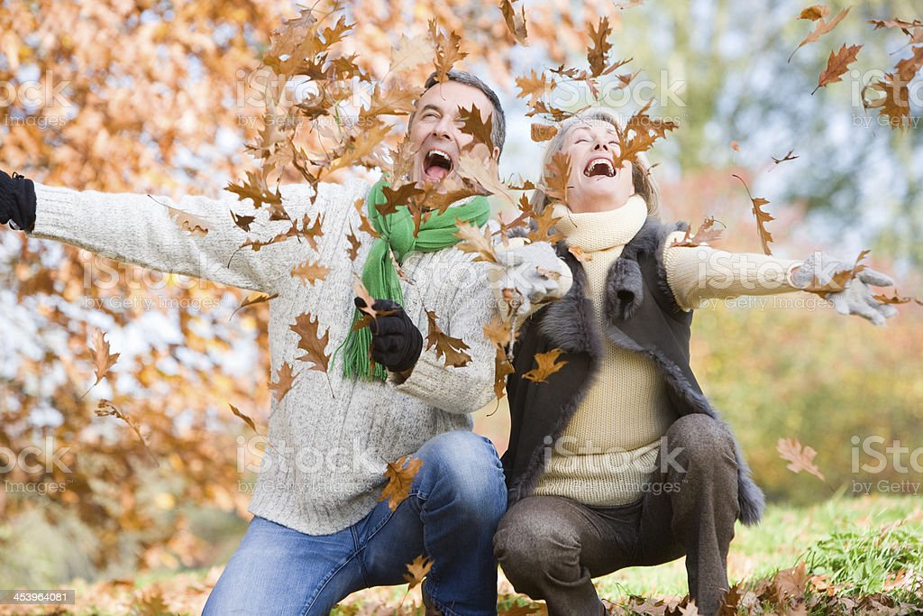Senior couple throwing leaves in the air royalty-free stock photo