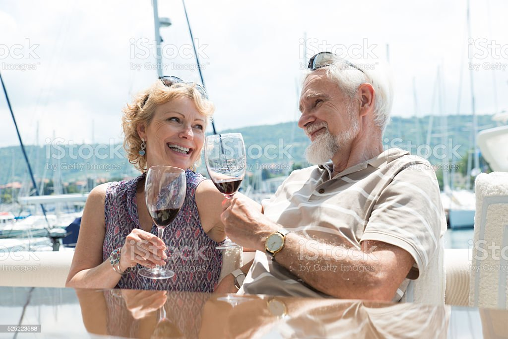 Senior couple toasting on a yacht stock photo