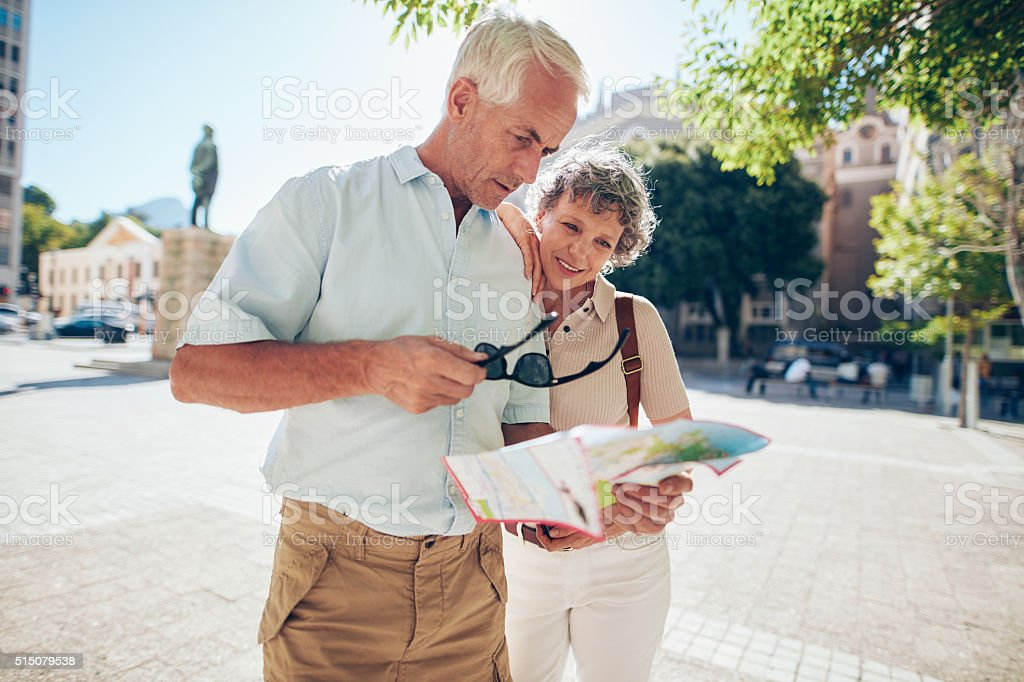 Senior couple trying to read street map stock photo