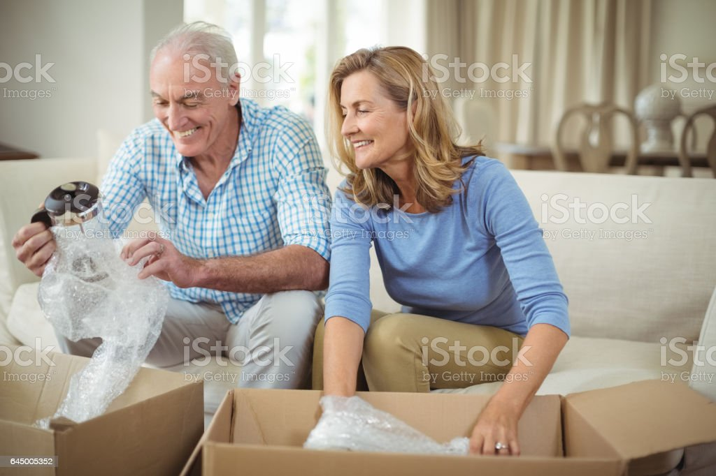 Senior couple unpacking carton boxes in living room stock photo
