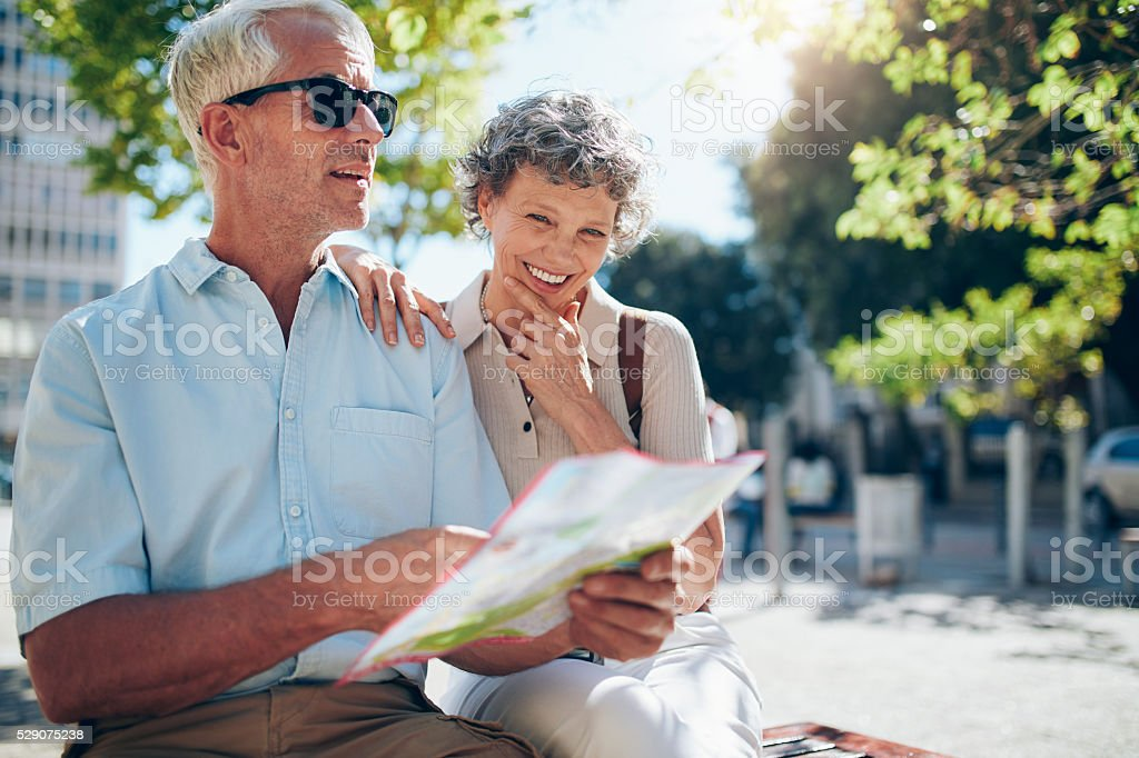 Senior couple using a city map for location stock photo