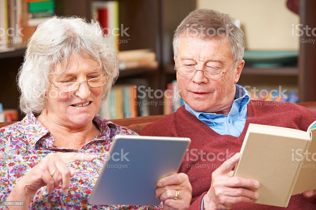 Senior Couple Using Digital Tablet And Reading Book stock photo