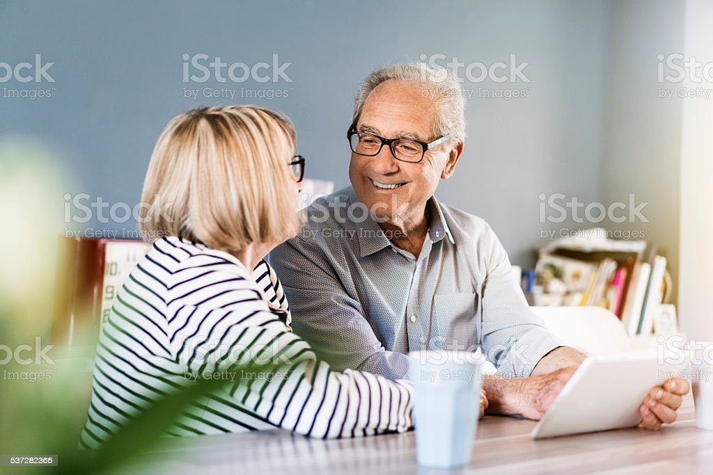 Senior couple using digital tablet at home stock photo