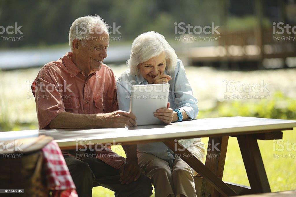 Senior Couple Using Digital Tablet In Park royalty-free stock photo