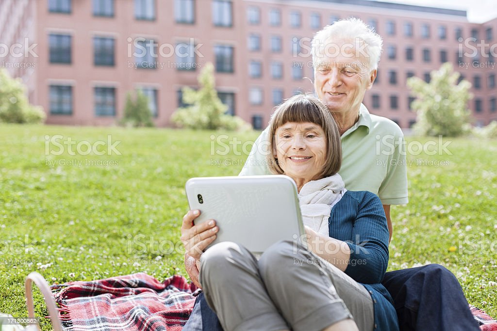 Senior couple using digital tablet outdoors royalty-free stock photo