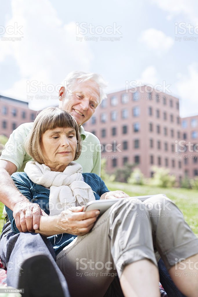 Senior couple using digital tablet outdoors stock photo