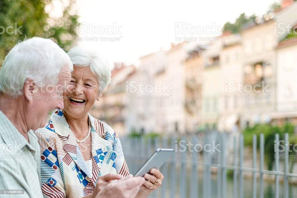 Senior couple using digital tablet together stock photo