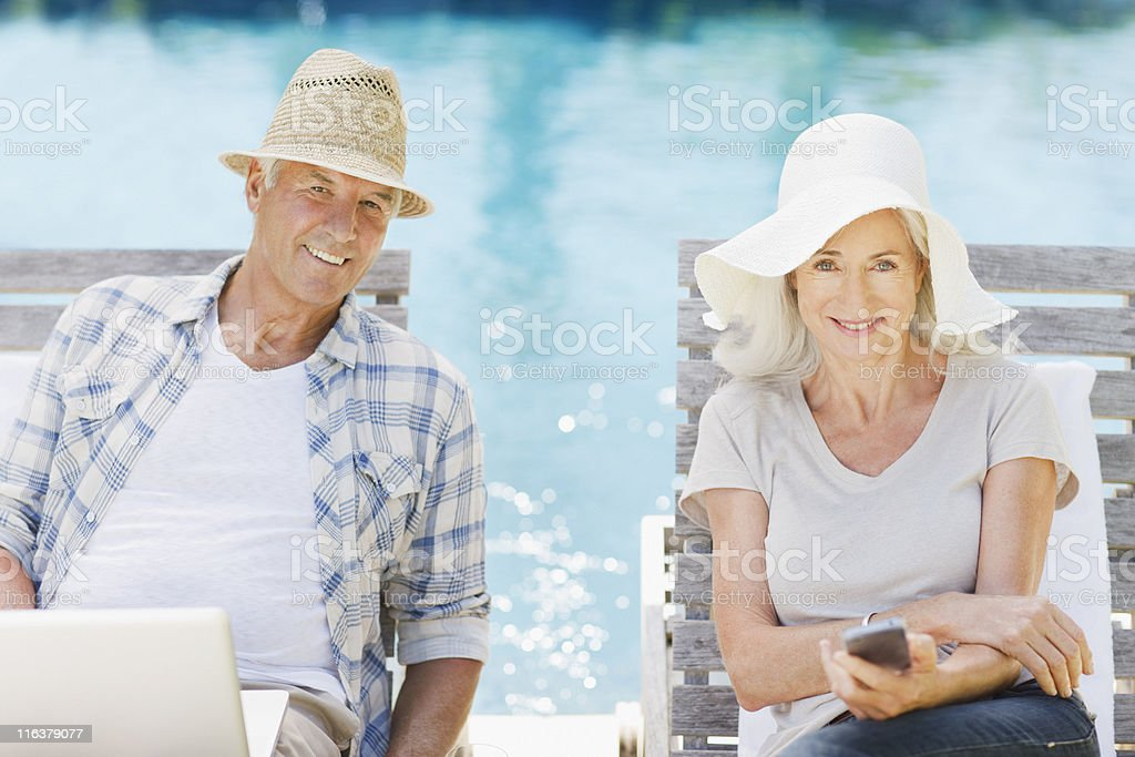 Senior couple using laptop and cell phone at poolside royalty-free stock photo